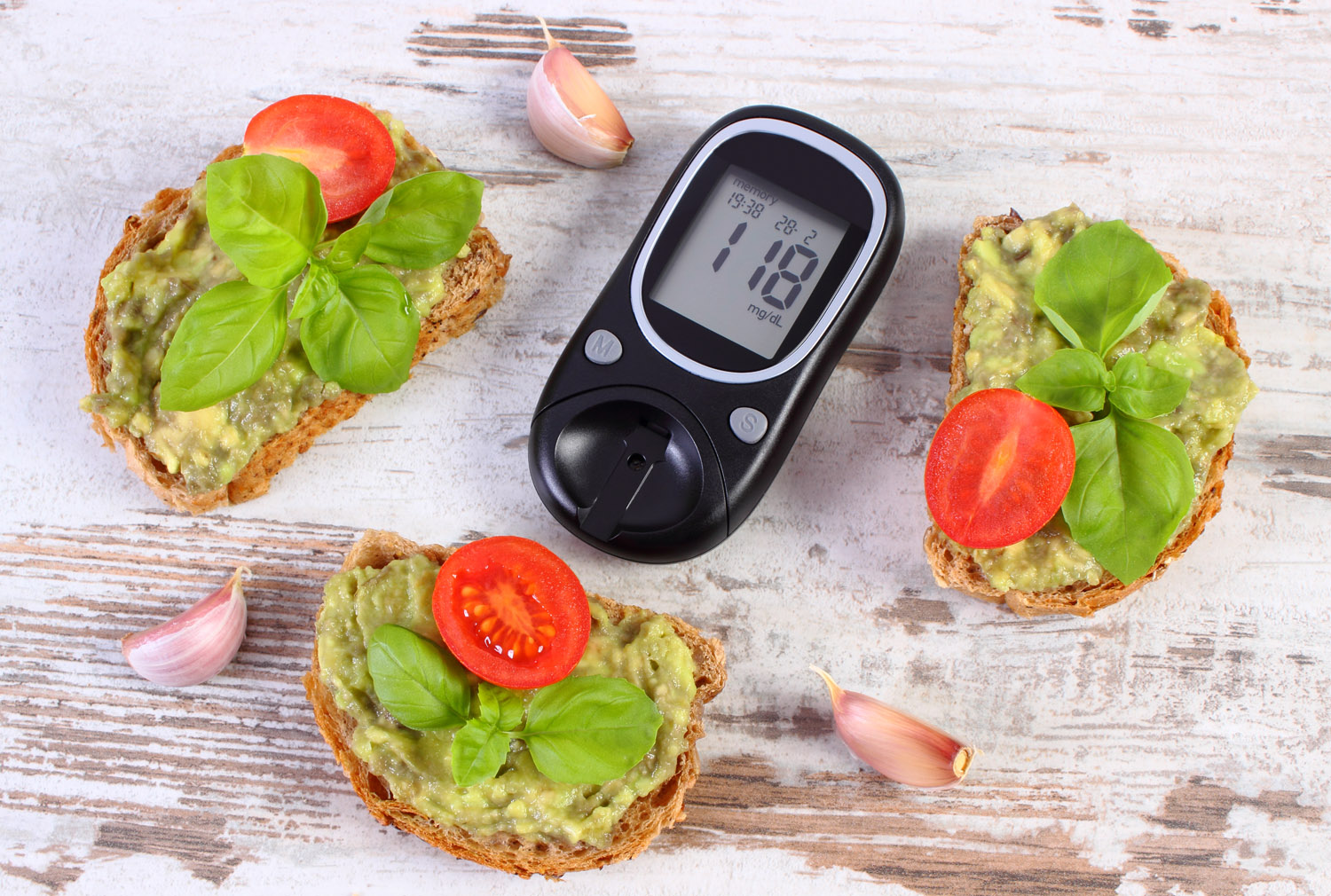Glucose meter with result of measurement sugar level and freshly sandwiches with paste of avocado, concept of diabetes, healthy food, nutrition and omega fatty acids