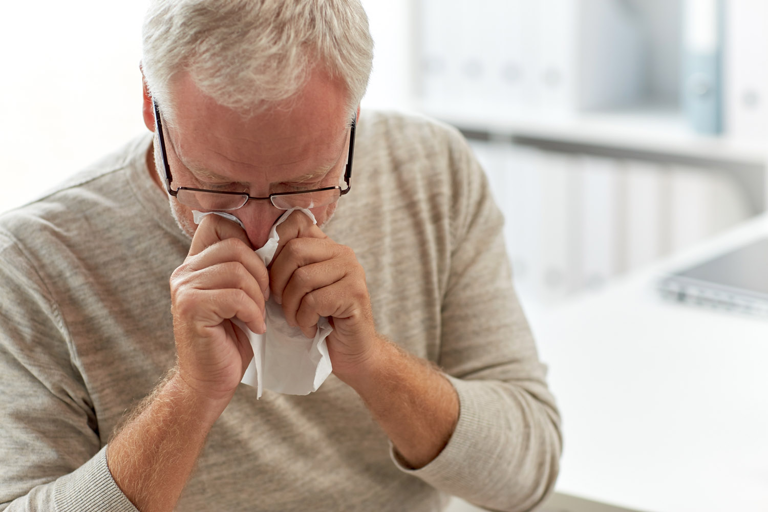 medicine, healthcare, flu and people concept - senior man blowing nose with napkin at medical office at hospital