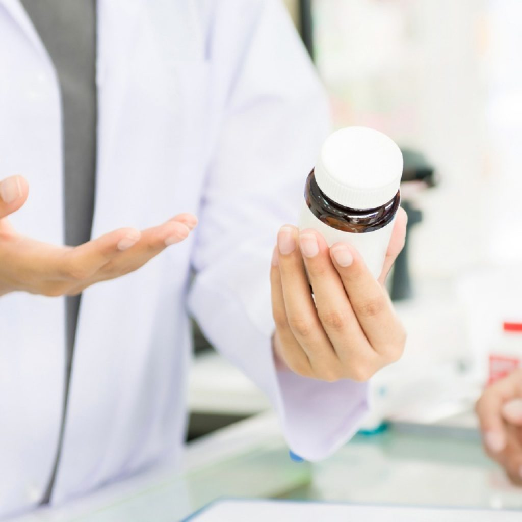 female-pharmacist-holding-medicine-bottle-giving-advice-to-customer-picture-id876037360